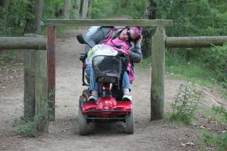 A lady using an electric scooter on an outdoor park pathway, path has a fence opening, with a piece of timber over the path at head height and she is trying to get under