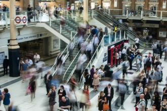 A slightly blurred image of a London underground station, with people moving all directions