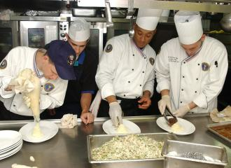 Chefs wearing white, working in a kitchen together preparing food