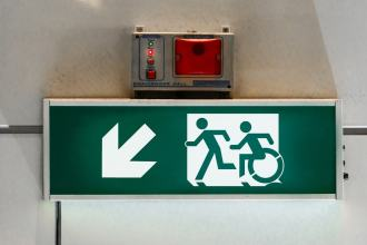 Illuminated exit sign with the running man type pictogram and a similar person using a wheelchair pictogram