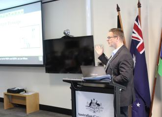 Lee Wilson presenting to Government departments, standing behind lecturn, with Australian National flag and Indigenous Australian flag