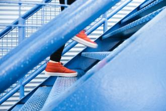 Person in red shoes walking up a steel staircase, close up of feet only