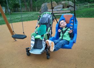 Child with disability, in an accessible swing in a playground, with the stroller next to the swing, the child is smiling happily