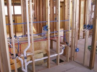 Domestic house being built at frame stage with plumbing roughed in