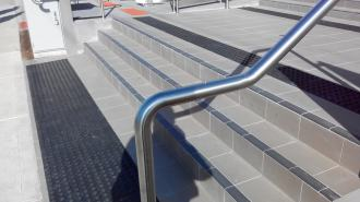 External stair handrail with tactile button near the end