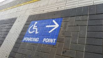 Railway station platform, showing tactile ground surface indicators and white International Symbol of Access on blue background with arrow and words BOARDING POINT