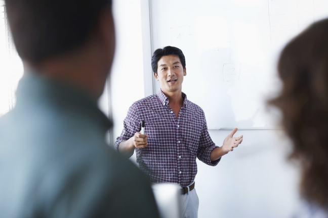 Business man standing in front of a whiteboard looking at two people