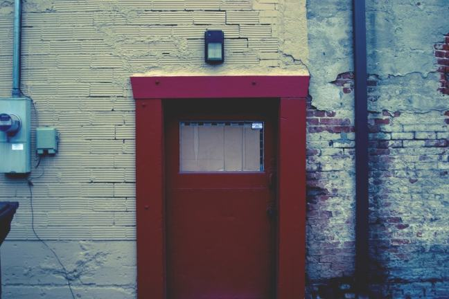 Old red door in a white washed brick wall