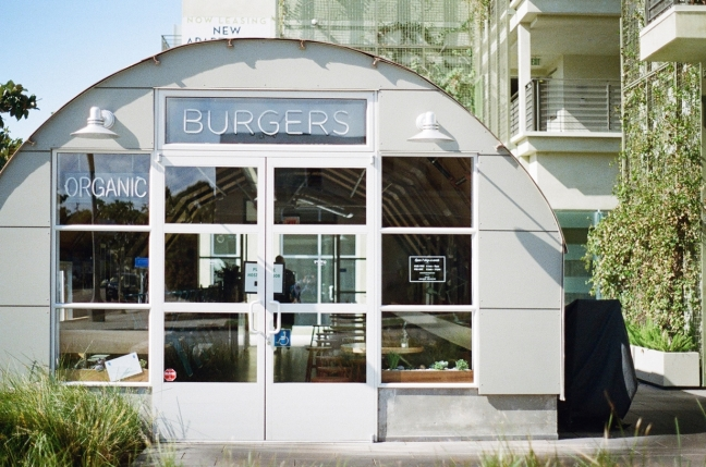 The entrance to a small fast food business, with a sign over the door saying BURGERS