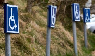 4 disabled parking signs on posts