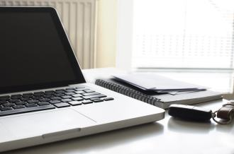 Laptop on desk with notebook and car keys