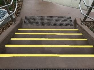Yellow stair tread nosing strips on brown coloured concrete, view looking down on treads