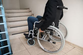 A man in a wheelchair approaches the bottom of some stairs