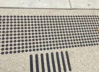 Black discrete tactile indicators on light exposed stone concrete.jpg